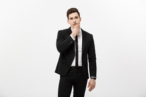 Business Concept: Young handsome man in black suit looking at copy-space smiling, thinking or dreaming
