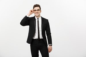 Business Concept: Young handsome businessman wearing glasses holding hand in pocket isolated on white background.