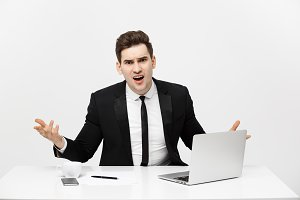 Business Concept: Portrait of screaming angry businessman sitting in office isolated over white background.