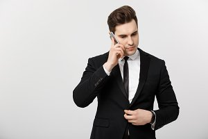 Business Concept: Portrait of young handsome businessman talking on mobile phone with serious and stress expression. Isolated over white background.