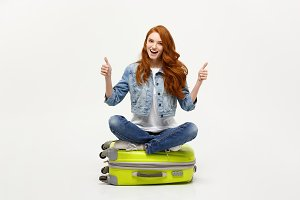 Traveling and Lifestyle concept. Young excited caucasian woman sitting on the luggage valise showing thumb up. Isolated on white. Ready for vacation.