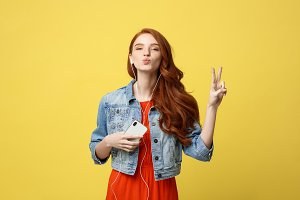 Liftstyle: Portrait of a pretty smiling caucasian woman in headphones listening to music and showing peace gesture isolated over yellow background