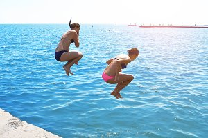 two girlfriends jump into the ocean