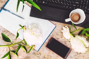 white peonies on the desktop. work a