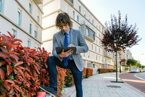 Businessman working with the tablet in the street