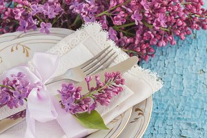 Tableware and bouquet of lilacs