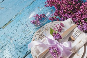 Tableware and bouquet of lilac