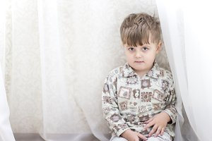 Little boy near a white curtains.
