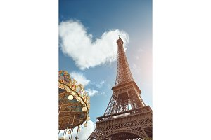 Eiffel tower and carousel and heart shape in clouds