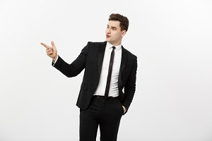 Business Concept: Close up portrait of young successful brunete stock-market broker guy or businessman pointing on a copyspace with his finger on white background.
