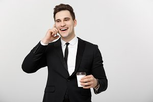 Business Concept: Close-up confident young handsome businessman talking on cell phone and drinking coffee over white isolated background.