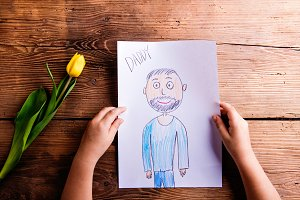 Girl holding drawing of her father and yellow tulip.