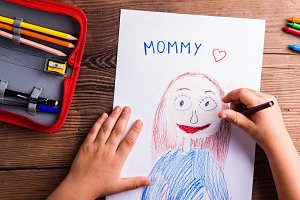 Unrecognizable girl drawing picture of her mother. Wooden backgr