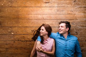 Beautiful young couple hugging against wooden background