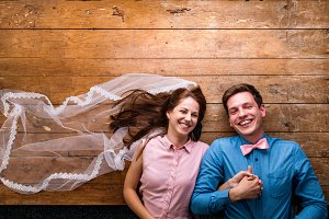 Young couple lying on a floor against wooden background