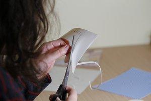 Female hands cutting a paper