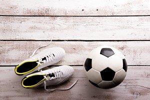 Soccer ball, cleats on white wooden floor, studio shot