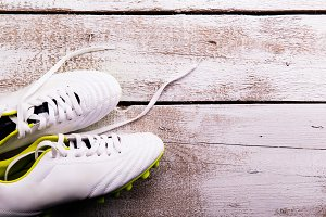 Soccer cleats against wooden background. Studio shot. Copy space.