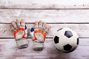 Soccer ball, gloves on white wooden floor, studio shot