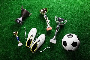 Soccer ball, cleats and trophies against green artificial turf