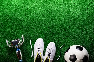 Soccer ball, cleats and trophy against green artificial turf