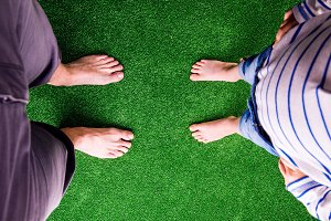 Unrecognizable father and son standing, against artificial green