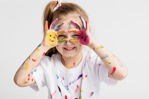 Little girl covered in paint making