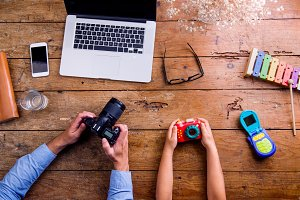 Father and son holding cameras, old wooden office desk