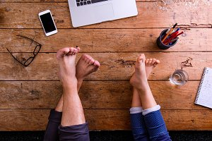 Legs of father and son, office desk, smartphone, notebook