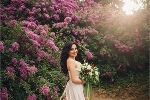 beautiful woman in a luxurious dress is standing in a blooming lilac garden