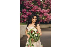 young bride in a luxurious dress is standing in a blooming lilac garden