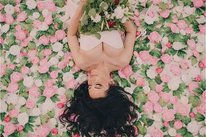 young bride lies on flowers and holds bouquet in her hands, top view