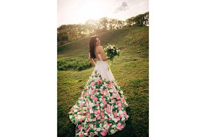young bride in a dress from flowers walking on grass and smiling