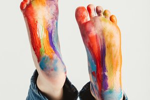 Kid's feet painted in rainbow colors
