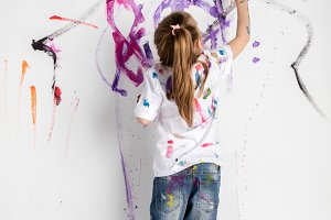 Little girl decorating a white wall