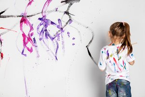 Little girl painting a white wall wi