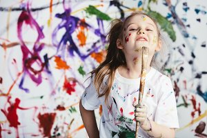 Young child painter standing with a
