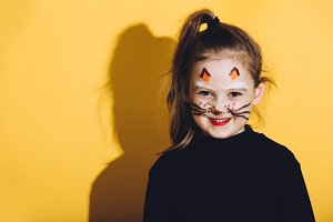 Little girl with cat makeup on her f