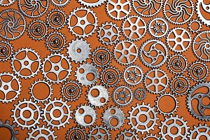 Bunch of cogwheels on an orange back