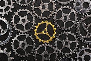 Golden cogwheel surrounded by metal
