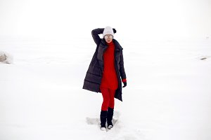 girl stands in a snowy field in a jacket