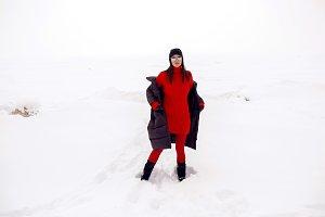 girl running in a snowy field in a jacket