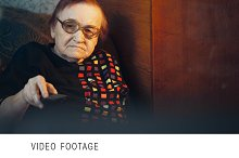 Elderly woman in glasses watching TV