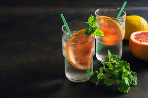 Refreshing cocktail with grapefruit and mint. Glass misted with cold water and a slice of grapefruit. Dark background, backlight. Place for text.