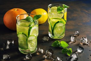 Detox water with cucumber, lime and mint on a rustic background with backlighting.