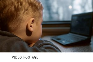 Little boy watching video on laptop