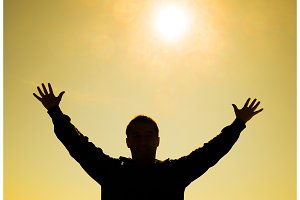 Silhouette of a man against the background of the sun and yellow at sunset sky. Hands are raised up to the sun