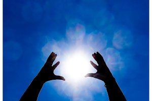 Silhouette of hands against sun and blue sky background. Hands are raised up to the sun