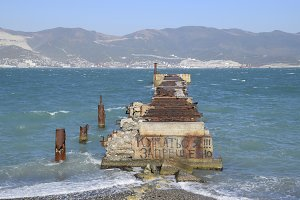 Old dismantled rusty pier. The inscription: it is forbidden to swim. The destroyed pier