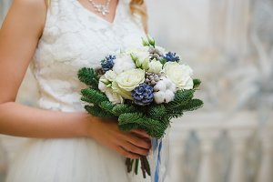 Wedding bouquet of pine needles, cones and white roses in the hands of the bride